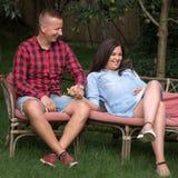 Heterosexuella par av den vuxna mannen och gravida kvinnan i trädgård fotografering för bildbyråer