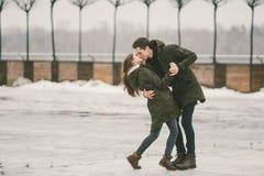 Heterosexuella parungdomarförälskade studenter en man och en Caucasian kvinna I vinter i stadsfyrkanten som täckas med is, arkivbilder