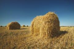 Heuballen auf Feld mit Weizenstroh und -himmel im Ackerland an s Stockbilder