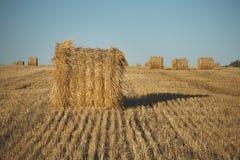 Heuballen auf Feld mit Weizenstroh und -himmel im Ackerland an s Stockfotos