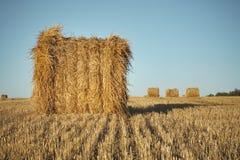 Heuballen auf Feld mit Weizenstroh und -himmel im Ackerland an s Lizenzfreies Stockfoto