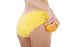 Heup, benen, buik en sinaasappel ter beschikking. stock foto's