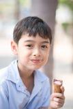 Heure d'été de faveur de fraise de cornet de crème glacée de consommation de petit garçon images stock