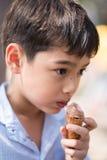 Heure d'été de faveur de fraise de cornet de crème glacée de consommation de petit garçon photos stock