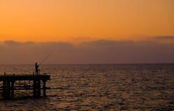Heure d'or de pêcheur solitaire Photographie stock