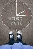` Heure d ete, FrenchDaylight-Einsparungs-Zeit auf Asphalt mit Schuh zwei Stockbilder