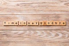 Heure de dire au revoir le mot écrit sur le bloc en bois Heure de dire au revoir le texte sur la table en bois pour votre desing, image libre de droits