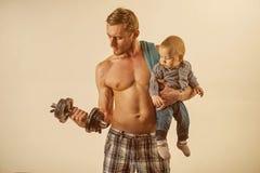 Heure de folâtrer Triceps de biceps de construction de père avec le fils Style de vie sain de famille Homme fort avec le bébé gar photographie stock