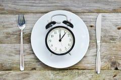 Heure de manger avec la fourchette et le couteau de plat d'horloge sur une table images stock