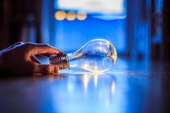 Heure pour des id?es, l'inspiration et l'invention : Les mains tiennent une ampoule de LED photographie stock