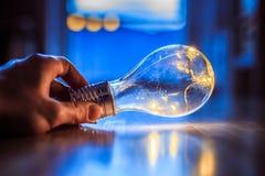 Heure pour des id?es, l'inspiration et l'invention : Les mains tiennent une ampoule de LED photos stock