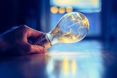 Heure pour des id?es, l'inspiration et l'invention : Les mains tiennent une ampoule de LED photos libres de droits
