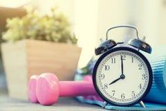 Heure pour exercer l'horloge et l'haltère sur la table image stock