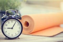 Heure pour exercer l'horloge et le tapis de yoga photographie stock
