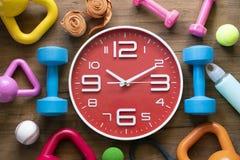 Heure pour exercer l'horloge, l'haltère, et l'équipement de sport image libre de droits