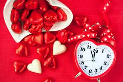 Heure pour l'amour doux Horloge en forme de coeur rouge avec des chocolats Photographie stock libre de droits