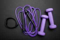 Heure pour la forme physique Accessoires de sports sur un fond noir Corde de saut, haltères et bracelet de forme physique photo libre de droits