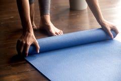 Heure pour la pratique, mains femelles déroulant le tapis bleu de yoga image stock
