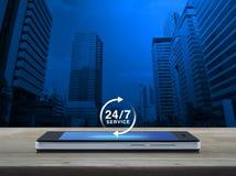 24 heures entretiennent l'icône sur l'écran intelligent moderne de téléphone sur la table Images stock