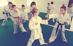 Heureuse boxe d'entraînement d'enfants dans les paires dans la classe de karaté images stock
