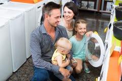 Heureuse famille adulte choisissant la machine à laver Photographie stock libre de droits