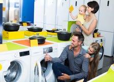 Heureuse famille choisissant la machine à laver Photos stock