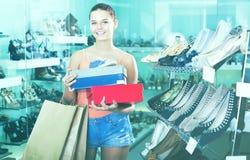 Heureuse femelle d'adolescent tenant des boîtes dans la boutique de chaussures Photos libres de droits