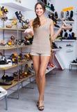 Heureuse femme adulte se tenant avec la chaussure choisie Image stock