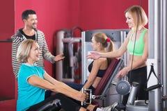 Heureuse formation active d'haltérophilie de personnes dans le club de santé Image stock