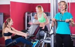 Heureuse formation active d'haltérophilie de personnes dans le club de santé Images libres de droits
