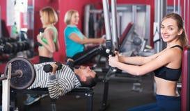 Heureuse formation satisfaisante positive d'haltérophilie de personnes dans le club de santé Image stock