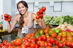 Heureuse jeune femme sélectionnant les tomates fraîches Photos libres de droits