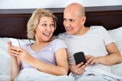 Heureuse mise en réseau sociale mûre de sourire de couples ensemble Photo libre de droits