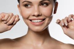 Heureuses dents de nettoyage de fille par le fil spécial Image libre de droits