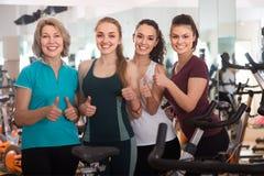 Heureuses femelles de la formation différente d'âge sur des vélos d'exercice Photos stock