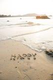 Heureux écrit dans le sable à la plage ondule à l'arrière-plan Photos stock