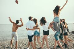 Heureux équipe et la promenade de la femme au groupe de plage d'amis appréciant des vacances de plage image libre de droits