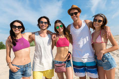 Heureux amis se reposant sur la plage Photos libres de droits