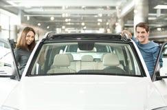 Heureux avec leur nouvelle voiture. Jeunes couples heureux tenant aux les deux le SI photo stock