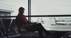 Heureux chez un bon homme d'humeur s'asseyant sur les chaises d'aéroport attendant son vol il à l'aide d'un ordinateur portable p clips vidéos