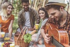 Heureux compagnons appréciant la nourriture et la musique dehors Images stock