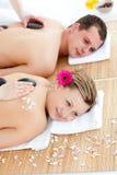 Heureux couples recevant le massage arrière avec les pierres chaudes Photos stock