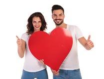 Heureux dans des couples d'amour tenant le coeur et faites le signe correct Images stock