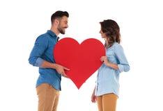 Heureux dans des couples d'amour tenant le grand coeur rouge Image stock