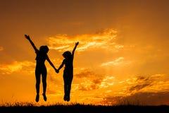 Heureux de deux femmes sautant et de silhouette de coucher du soleil Photos libres de droits