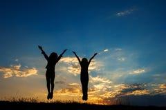 Heureux de deux femmes sautant et de silhouette de coucher du soleil Images stock