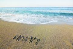 Heureux de mot écrit sur le sable de plage   Image stock