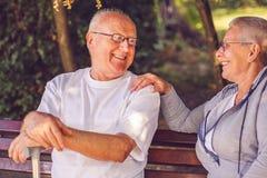 heureux ensemble Couples supérieurs de sourire se reposant sur un banc de parc photographie stock