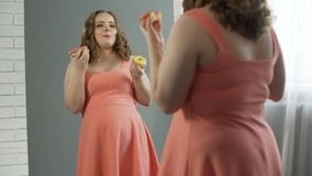 Heureux et satisfaisant avec la fille surdimensionnée de corps mangeant des butées toriques devant le miroir banque de vidéos