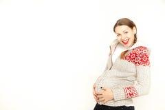 Heureux, femme enceinte de jeunes dans un habillement d'hiver sur un fond blanc Photo libre de droits